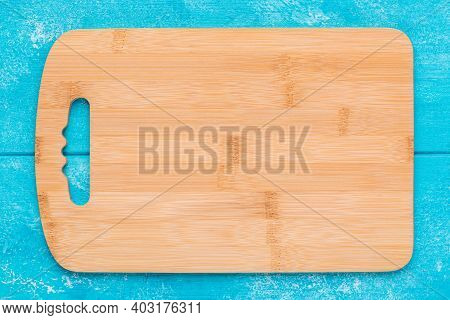 New Rectangular Wooden Bamboo Cutting Board On Blue Wooden Table. Mockup For Food Project. Top View.