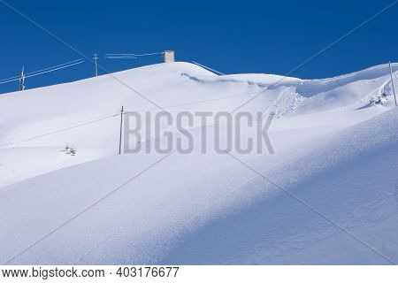 Snowfall. Pristine Deep White Snow Drifts. Sun Reflects On The Snow In The Winter Alps.