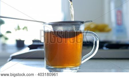 Image With Making A Hot And Aromatic Tea Using A Strainer And Natural Tea Leafs