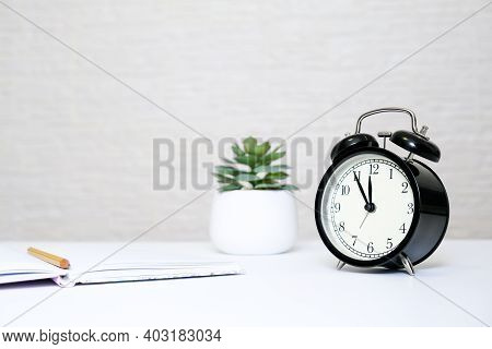 Alarm Clock Showing 5 Minutes To Twelve And A Notebook With A Yellow Pencil As A Concept Of Business