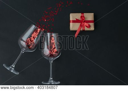 Top View Of Two Wine Glasses With Little Red Heart Sparkling Confetti And Wrapped Giftbox On Black B