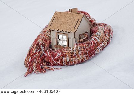A Wooden House Stands In The Snow, Wrapped In A Knitted Scarf, The Concept Of A Heating Season, Cold