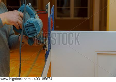Wood Siding Contractor Using An Electric Compound Miter Saw To Cut Door Trim Boards In The Construct