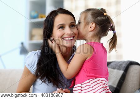 Portrait Of Smiling Mother Listening To Daughter. Happy Girl Whispering In Ear Of Cheerful Mommy. Ch