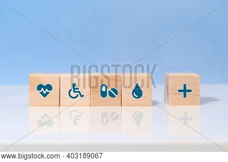 Choose A Emoticon Icons Healthcare Medical Symbol On Wooden Block. Healthcare And Medical Insurance