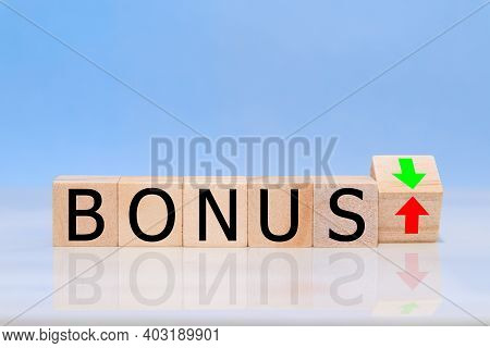 Wooden Cubes Are Turned Over  And Changes The Direction Of An Arrow, Symbolizing That The Bonus Is G