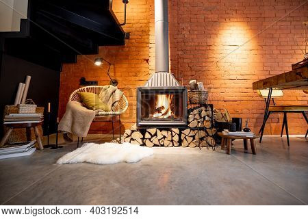 Cozy Fireplace With Firewood In The Loft Style Home Interior With Brick Wall Background, Burning Fir