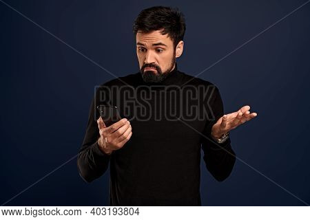Isolated On Pacific Blue, Angry Annoyed Man Frowns Look At Smart Phone Having Problems With Wi-fi No