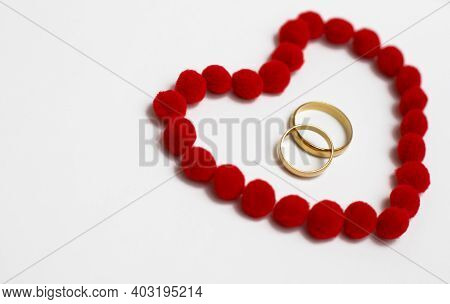 Gold Wedding Rings In Red Heart. Wedding Rings On The White Background, Surrounded By The Heart. Sym