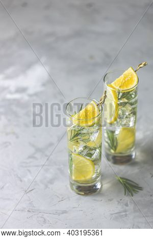 Two Glasses Of Refreshing Lemon Lime Drink With Ice Cubes In Glass Goblets With Water Drops Against