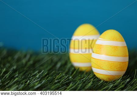 Easter Holiday. Easter Yellow Striped Eggs In Green Grass On A Blue Turquoise Background.spring Fest