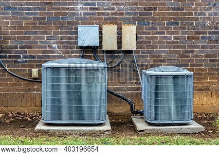 Horizontal Close-up Shot Of Air Conditioning Units Outside Of A Small Brick Office Building.