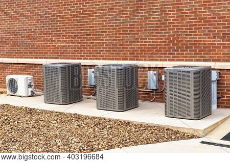 Horizontal Shot Of Commercial Heating And Air Conditioning Units Against A Brick Wall.