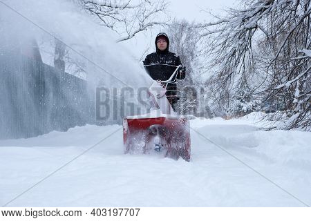 Young Man Clearing Snow In His Backyard With Wheeled Snow Blower