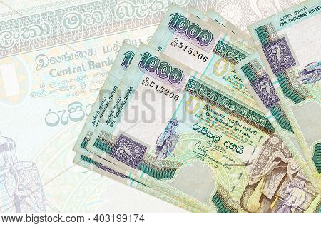 1000 Sri Lankan Rupees Bills Lies In Stack On Background Of Big Semi-transparent Banknote. Abstract