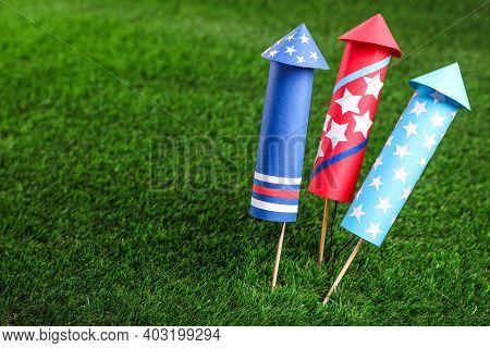 Firework Rockets On Green Grass, Closeup. Space For Text