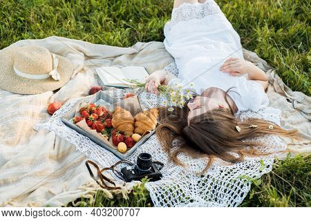 Field In Daisies, A Bouquet Of Flowers.summer Picnic By The Sea. Basket For A Picnic With With Buns,