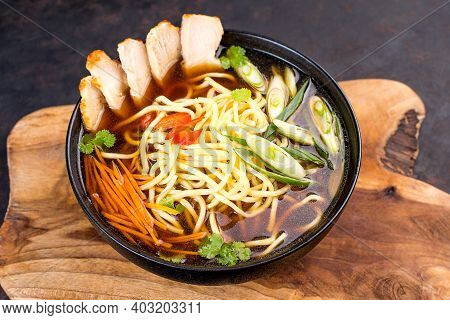 Chinese Noodles With Pieces Of Meat And Vegetables In A Black Bowl On The Kitchen Board.stir-fried C