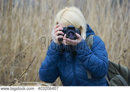 Close Up Portrait Of Female Photographer Taking Photos With Digital Camera. Girl Photographer With A