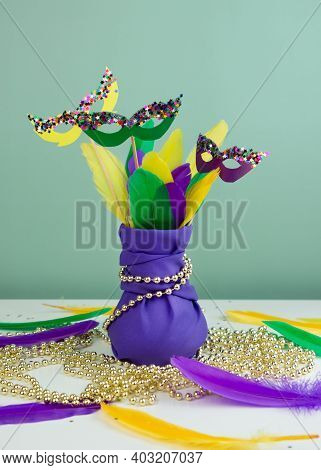 Mardi Gras Decoration. Bouquet Of Multicolored Feathers And Masks In Violet Cloth Vase. Party Invita