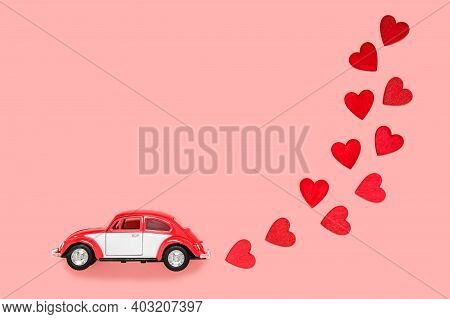 Fulda, Germany - Dec 18, 2020: Small Retro Toy Car With Many Red Hearts For Valentines Day On Pink B
