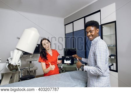 Happy Doctor And Patient In Modern Urology Clinic. Young Female Doctor And Her Male African Patient,