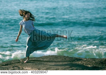 A woman is engaged in choreography on the ocean coast.