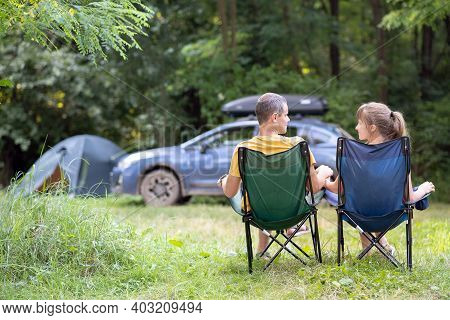Back View Of A Happy Couple Sitting On Chairs At Campsite Relaxing Together. Travel, Camping And Vac