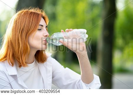 Happy Thirsty Redhead Woman Drinking Fresh Bottled Water In Summer Outdoors.