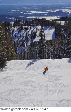 A Single Skier Swooshing Down Slope Towards The Chair Lift