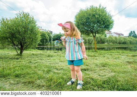 Beautiful Baby Girl Blowing Soap Bubbles In The City Park Ureki. Ecology And Nature Outdoors. Hot Su