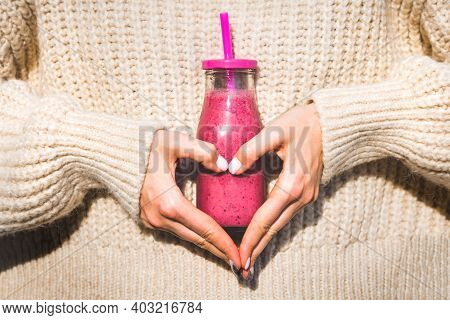 Woman In Woollen Sweater Making Heart Shape With Her Hands And Holding Bottle With Pink Homemade Det