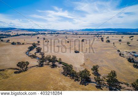 Small Creek Passing Through Agricultural Land With Hills On The Horizon In Australia - Aerial View