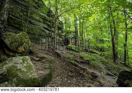 Dirt Trail Leads Up Through Rocky Cliff And Fallen Boulders In Cuyahoga Valley National Park