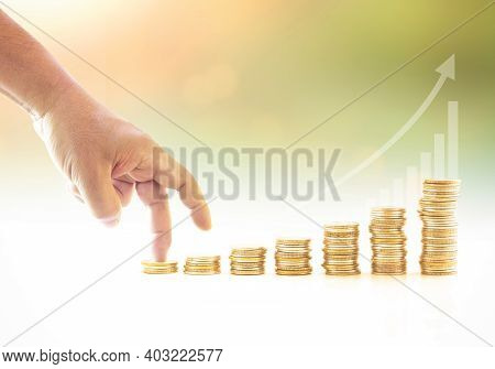 Fingers Walking Up On Stacks Of Gold Coins Over Graph Finance And Blurred Autumn Sunset Background