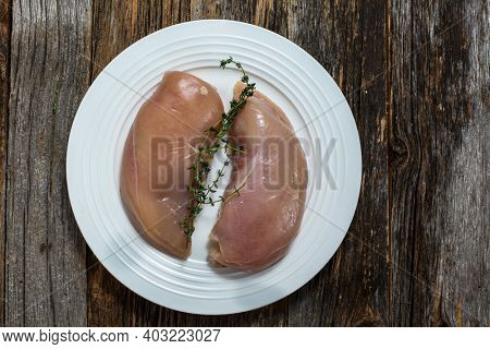 Chicken breast with thyme on plate table top view