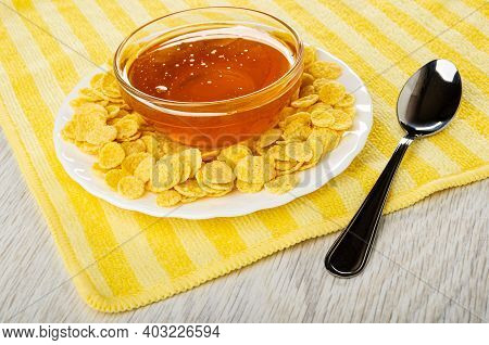 Transparent Bowls With Liquid Honey, Corn Flakes In White Plate, Teaspoon On Yellow Striped Napkin O