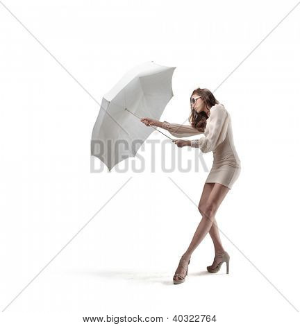 Beautiful woman in white with sunglasses repairing herself with an umbrella