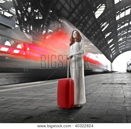 Beautiful woman in white with sunglasses standing with a red trolley near a leaving train