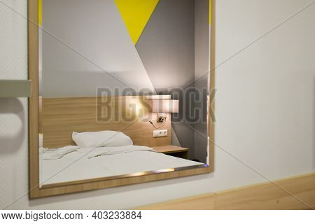 The Bedroom Interior Is Reflected In The Mirror On The Wall. Reflection In The Mirror: White Bed, Lu