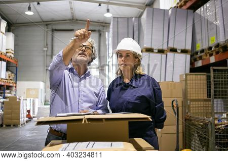 Mature Inspector Checking Warehouse, Pointing Up And Consulting Female Logistic Worker. Medium Shot,