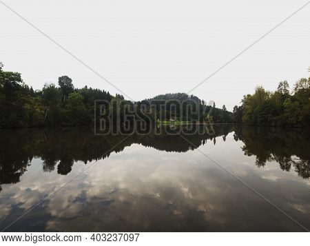 Mirror Reflection Of Calm Tranquil Green Forest Nature Landscape Lake Mitterteich Moosburg Carinthia