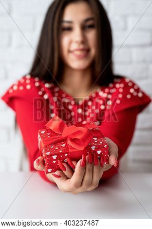 Young Romantic Woman In Red Dress Holding A Gift For Valentines Day Over White Brick Wall Background