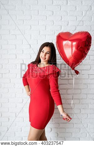Young Brunette Woman In Red Dress Holding A Red Heart Balloon
