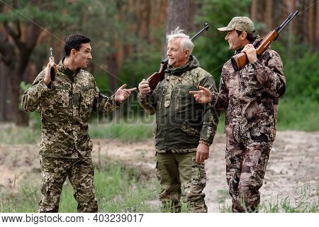 Happy Hunters In Forest Walking With Shotguns.