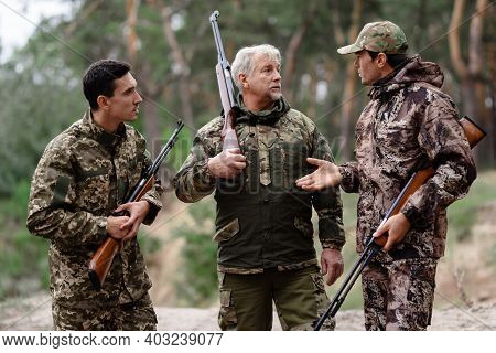 Family Of Hunters Talking In Forest Men Disagree.