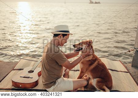 A Man Wear Straw Hat And Play With A Dog Pet Near The Sea Sunset. Travel, Vocation, Holiday Concept.