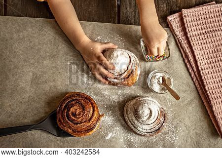 Children's Hands In The Frame Sprinkles A Fresh Baked Bun With Cinnamon With Pastry Sprinkles.