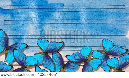 Bright Blue Morpho Butterflies On The Sheet Music. Old Music Sheet In Blue Watercolor Paint. Blues M