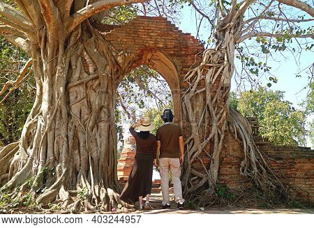 Couple Entering The Amazing Old Gate Of Wat Phra Ngam Temple Ruins In Ayutthaya, Historical Place In